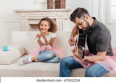 little african american girl singing while father playing guitar at home