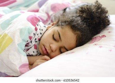 Little African American girl sleeping in bed