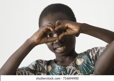 Little African black child showing heart symbol with his hands,