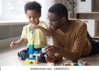 Little african boy building tower use colourful toy blocks set sitting on wooden warm heated floor in playroom with daddy or babysitter man, educational game, family at home leisure activities concept