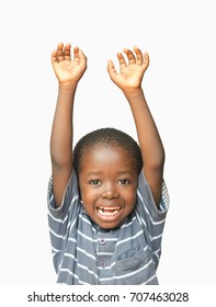 Little African boy holding his hands up in the air whilst laughing and smiling