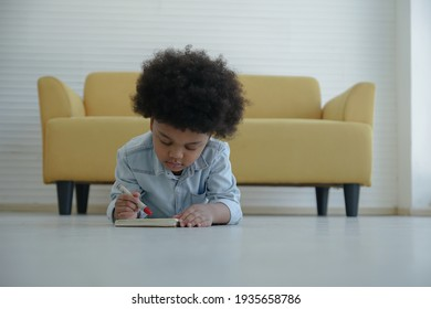 Little African boy holding red crayon in hand drawing coloring on book and lying on the floor at home