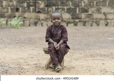 Little African Boy Sitting Outdoors posing with a big Smile on his Face