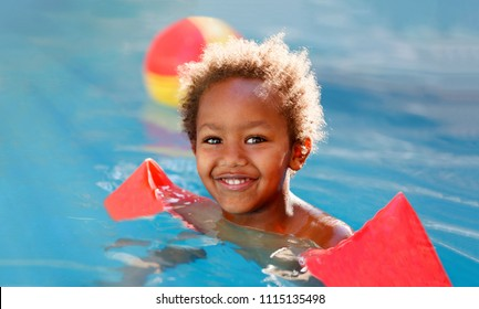 Little african child with orange sleeve floats in the pool