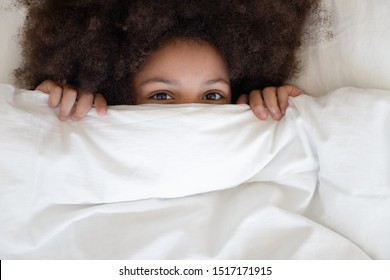 Little african girl with curly afro hairs hides behind blanket looks at camera, child lying in comfortable bed on white pillow peeking under warm duvet woke up in morning after sleep top close up view