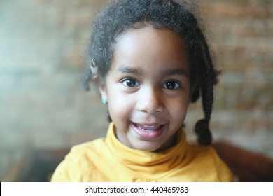 Little African girl is smiling and looking at camera.