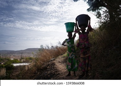 Little African Girls Walking with Heavy Water Buckets