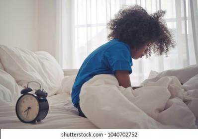Little african kid just woke up by alarm clock