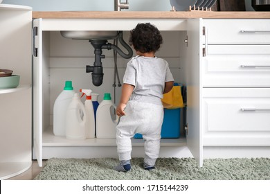 Little African-American baby playing with detergents at home. Child in danger - Shutterstock ID 1715144239