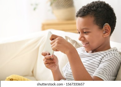 Little African-American boy with hearing aid using mobile phone at home