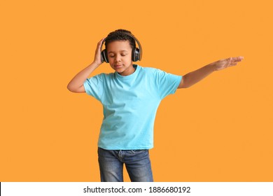 Little African-American boy listening to music and dancing against color background