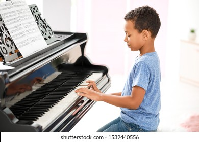 Little African-American boy playing grand piano at home