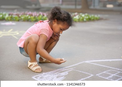 Little African-American child drawing house with chalk on asphalt