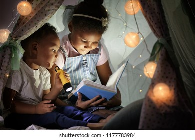 Little African-American children reading bedtime story in hovel
