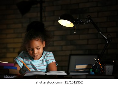 Little African-American girl doing homework in evening at home