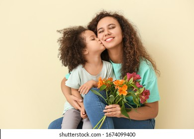 Little African-American girl with her mother and bouquet on color background