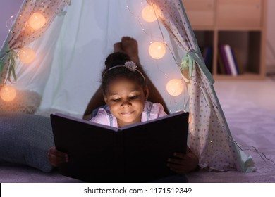 Little African-American girl reading bedtime story in hovel