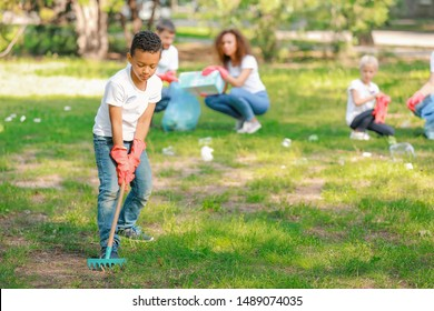 Little African-American volunteer gathering garbage in park