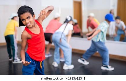 Little Afro boy hip hop dancer exercising with friends at dance class