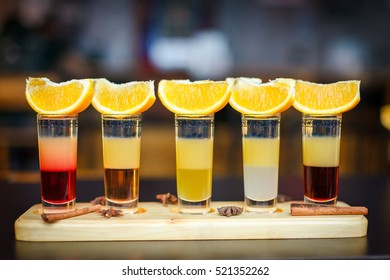 Little alcoholic cocktail at the bar. Multi-colored cocktail. Colorful cocktail at the bar. Orange on the cocktail. Cocktail on the side.