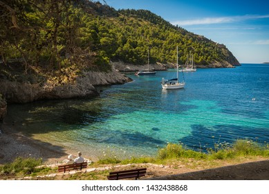 Little anchorage spot located in Assos, Greece, with several sailing boats anchored stern to with lines to the shore with turquoise waters and green hillside, and couple sitting on a park bench