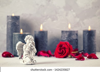Little angel , rose flower and burning candles on grey textured background. Card for mourning, death, sorrow.Selective focus. Place for text. Toned image.