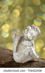 a little angel is sitting on a wooden board