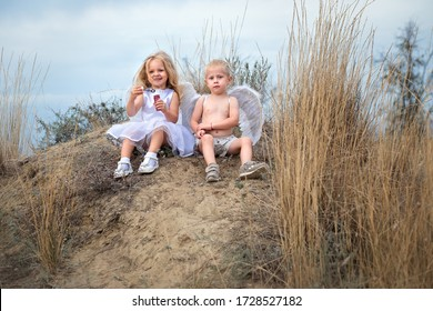 Little angels boy and girl sitting on a hill play soap bubbles. Girl's gonna blow soap balls.