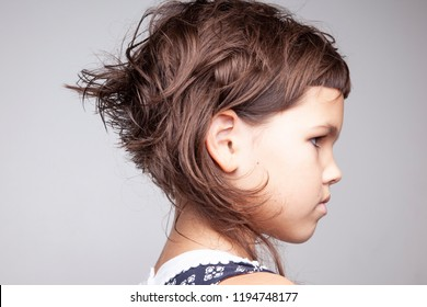 Little angry girl with stylish haircut, profile face