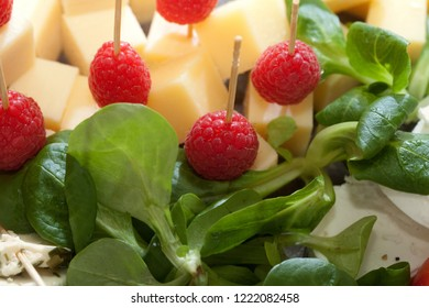 little appetizer sticks with gouda cheese and raspberries surrounded by some valerianella (corn salad) leaves