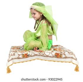 little arabian girl sitting on a flying carpet isolated on white background