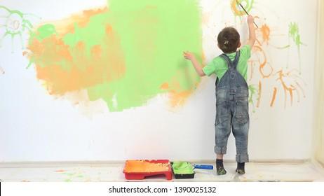 Petit artiste peignant un mur blanc, amusant enfant s'amuse