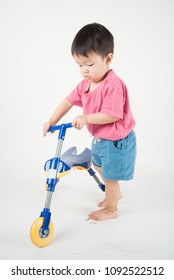 Little Asain baby toddler ride a tricycle bike on white background