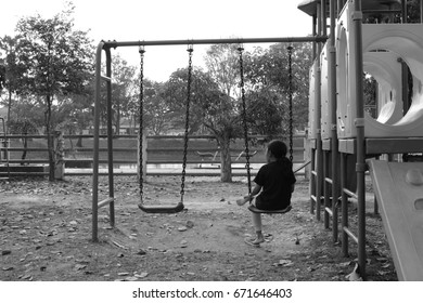 Little Asia girl sitting on the swing for wait somebody. Black and white tone. Lonely and sad.
