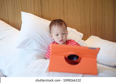 Little Asian 18 months / 1 year old baby boy child leaning against pillows on bed watching a video from tablet pc. Kids playing with tablet computer, Gadget-addicted children, pseudo-autism concept