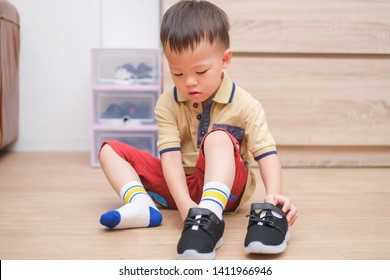 Little Asian 2 - 3 years old toddler boy sitting and concentrate on putting on his black shoes / sneakers, Get toddler out the door, Encourage Self-Help Skills in Children, Develop Confidence concept