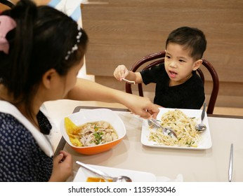 Little Asian baby, 30 months old, picking up a beansprout from her food (Padthai) and trying to negotiate with her mother that she does not want to eat it - baby refuses to eat vegetables