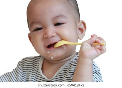 Little Asian baby boy enjoy eating,using spoon and smile.Isolated on white background