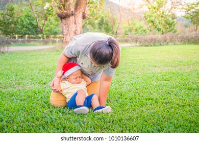 Little asian baby boy in Santa Claus hat crying on the ground while learning to walk with mother help at the park. Breastfeeding or early childhood development concept