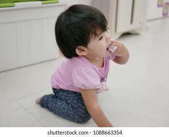 Little Asian baby girl, 13 months old, putting / eating a piece of straw plastic package picked from the floor - baby's choking hazard