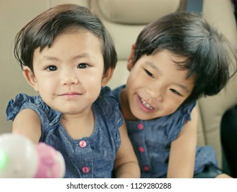 Little Asian baby girl, 15 months old (left), enjoying playing a doll with her older sister, 30 months old (right) - children's early relationships: siblings and friends