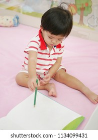 Little Asian baby girl, 15 months old, learning to hold a pencil and drawing on a book - pencil grasp development begins when children are babies