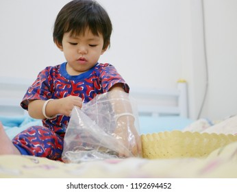 Little Asian baby girl, 17 months old, trying to take keys out of a plastic bag
