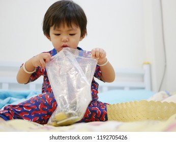 Little Asian baby girl, 17 months old, opening a plastic zip bag to look at keys inside