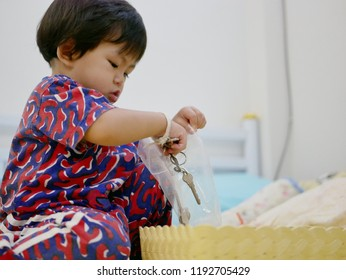 Little Asian baby girl, 17 months old, trying to put keys into a plastic bag