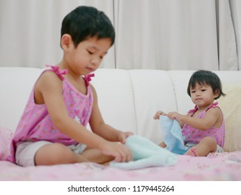 Little Asian baby girl, 18 months old, looking at her older sister folding clothes and try to do the same thing - child development by doing/imitating what the older one in the family does