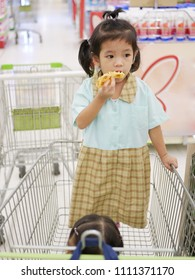 Little Asian baby girl, 29 months old, enjoy eating waffle on a shopping cart in a supermarket - giving something the baby likes to eat to make the baby enjoy waiting longer when parents do shopping