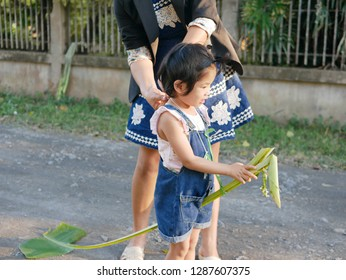 Little Asian baby girl, with help from her mother, getting ready to play Banana rib hobbyhorse riding ( Ma karn kluay ), one of several traditional  Thai games for children, at home