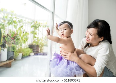Little asian baby girl at home in white room stands near window