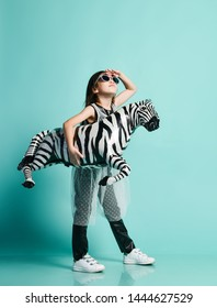 Little asian baby girl kid in high fashion clothes and sunglasses holds zebra metallic balloon under her arm and looks up in sky on mint background